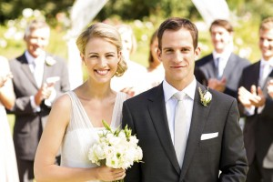 Portrait of happy newlywed couple with guests clapping in background during garden wedding. Horizontal shot.